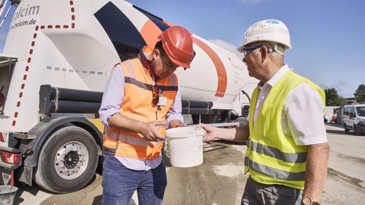 Florian Zettel, Leiter Kommunikation bei Via Solutions Nord, begleitet Andreas Michel, Holcim Produktmanager, bei der Zemententnahme für die spätere Qualitätskontrolle im Labor.