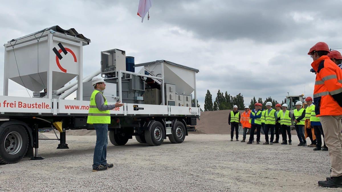 Simon Liebl, Leiter Business Development Holcim Deutschland (Bild links) erklärt die Funktionsweise des mobilen Betonwerks.